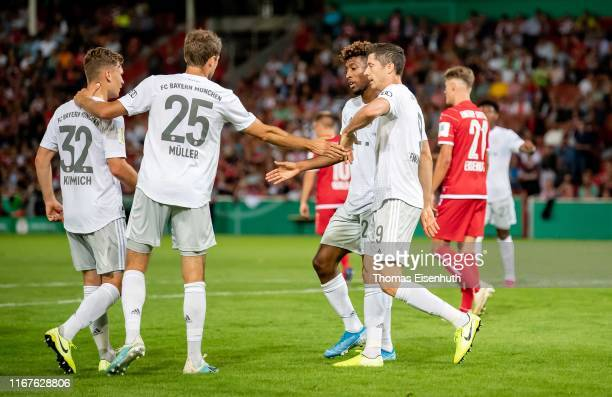 Robert Lewandowski of Muenchen celebrates with teammates after scoring his team's first goal during the DFB Cup first round match between Energie...