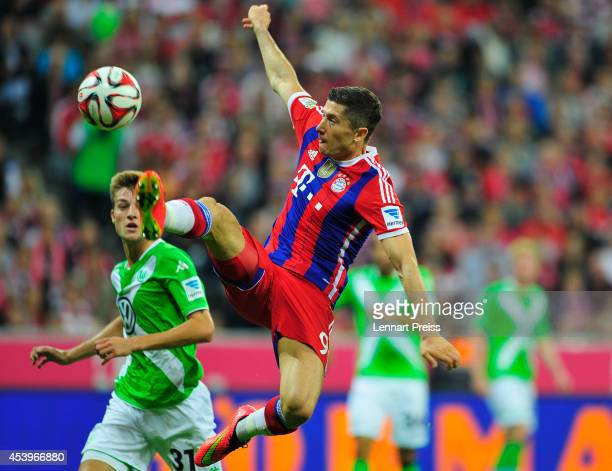 Robert Lewandowski of Muenchen challenges Robin Knoche of Wolfsburg during the Bundesliga match between FC Bayern Muenchen and VfL Wolfsburg at...