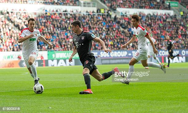 Robert Lewandowski of Muenchen is challenged by Christoph Janker of Augsburg during the Bundesliga match between FC Augsburg and Bayern Muenchen at...