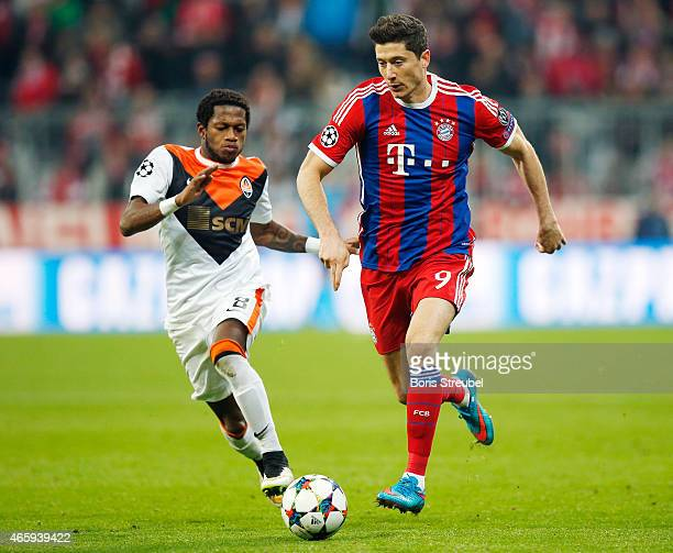 Robert Lewandowski of Muenchen is challenged by Fred of Donetsk during the UEFA Champions League Round of 16 second leg match between FC Bayern...