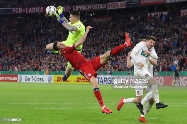 Robert Lewandowski of Muenchen is challenged by goalkeeper Kevin Mueller of Heidenheim during the DFB Cup quarterfinal match between Bayern Muenchen...