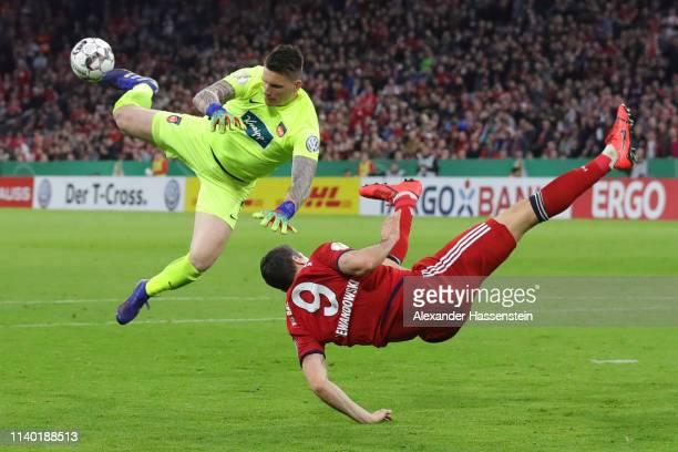 Robert Lewandowski of Muenchen is challenged by goalkeeper Kevin Mueller of Heidenheim during the DFB Cup quarterfinal match between Bayern Muenchen...