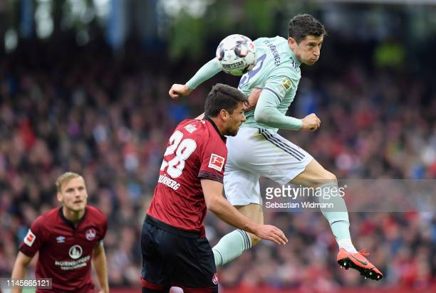 Robert Lewandowski of Muenchen is challenged by Lukas Mühl of Nuernberg during the Bundesliga match between 1 FC Nuernberg and FC Bayern Muenchen at...