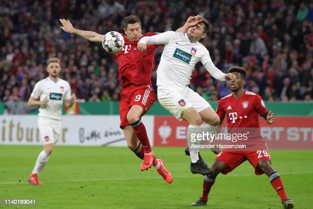 Robert Lewandowski of Muenchen is challenged by Marnon Busch of Heidenheim during the DFB Cup quarterfinal match between Bayern Muenchen and 1 FC...