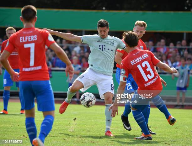 Robert Lewandowski of Muenchen is challenged by Soeren Behrmann of Drochtersen during the DFB Cup first round match between SV DrochtersenAssel and...