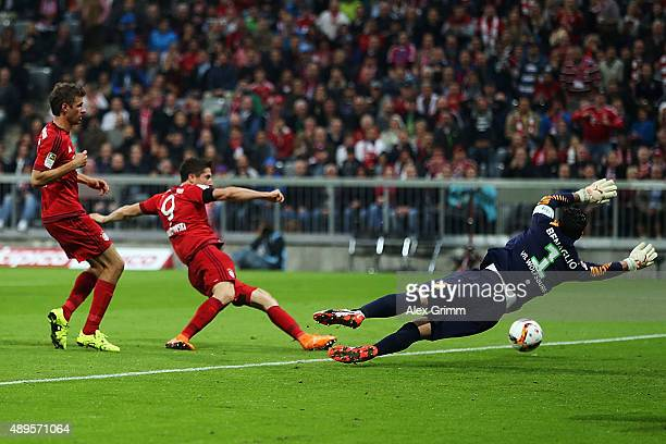 Robert Lewandowski of Muenchen scores his team's first goal against goalkeeper Diego Benaglio of Wolfsburg during the Bundesliga match between FC...