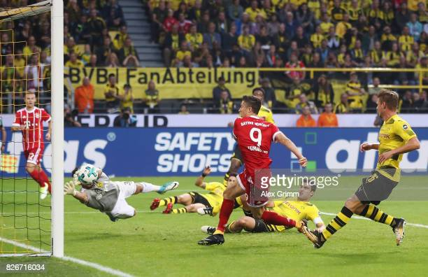 Robert Lewandowski of Muenchen scores his team's first goal past goalkeeper Roman Buerki of Dortmund during the DFL Supercup 2017 match between...