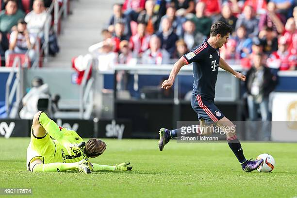 Robert Lewandowski of Muenchen scores his team's second goal against goalkeeper Loris Karius of Mainz during the Bundesliga match between 1 FSV Mainz...