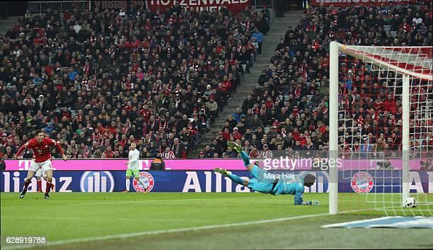 Robert Lewandowski of Muenchen scores his team's third goal against goalkeeper Diego Benaglio of Wolfsburg during the Bundesliga match between Bayern...