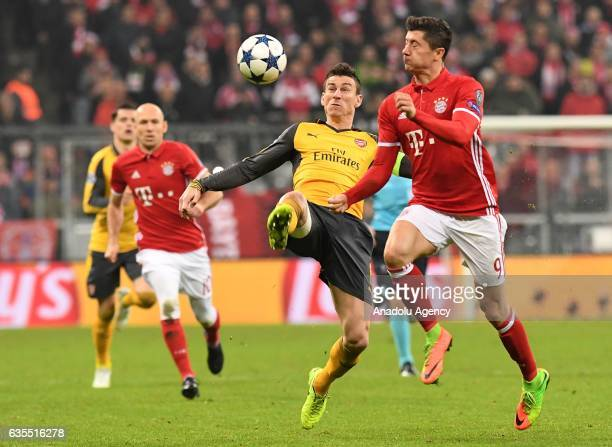 Robert Lewandowski of Munich and Laurent Koscielny of Arsenal vie for the ball during the UEFA Champions League round of 16 soccer match between FC...