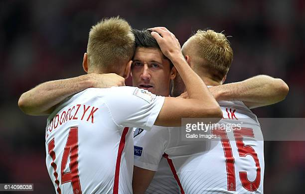 Robert Lewandowski of Poland celebrates his goal with Lukasz Teodorczyk of Poland and Kamil Glik of Poland during the Group E First Round World Cup...