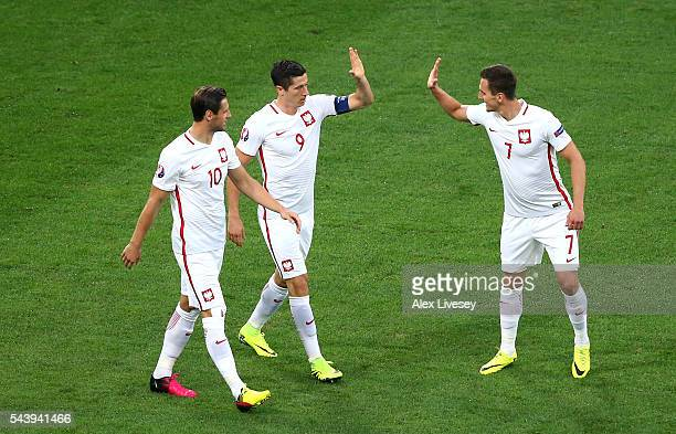 Robert Lewandowski of Poland celebrates scoring his team's first goal with his team mates Grzegorz Krychowiak and Arkadiusz Milik during the UEFA...