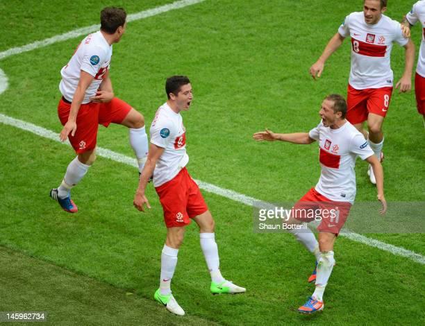 Robert Lewandowski of Poland celebrates scoring the opening goal with Sebastian Boenisch and Rafal Murawski of Poland during the UEFA EURO 2012 Group...