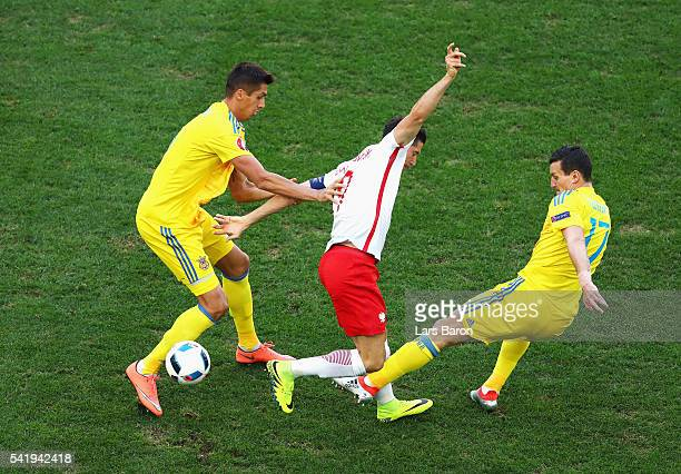 Robert Lewandowski of Poland controls the ball under pressure from Artem Fedetskiy of Ukraine during the UEFA EURO 2016 Group C match between Ukraine...