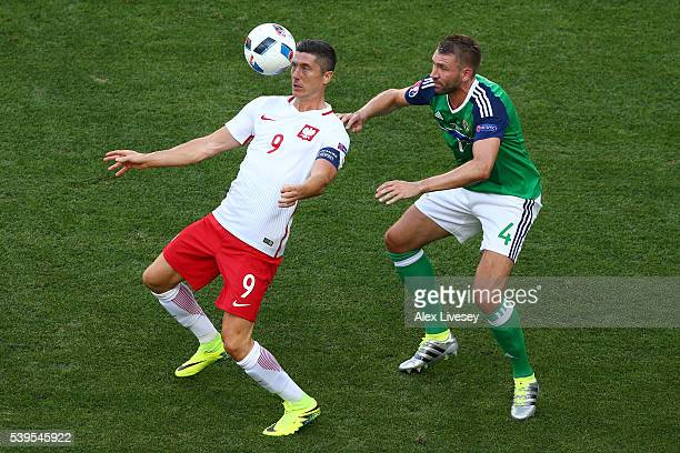 Robert Lewandowski of Poland controls the ball under pressure of Gareth McAuley of Northern Ireland during the UEFA EURO 2016 Group C match between...