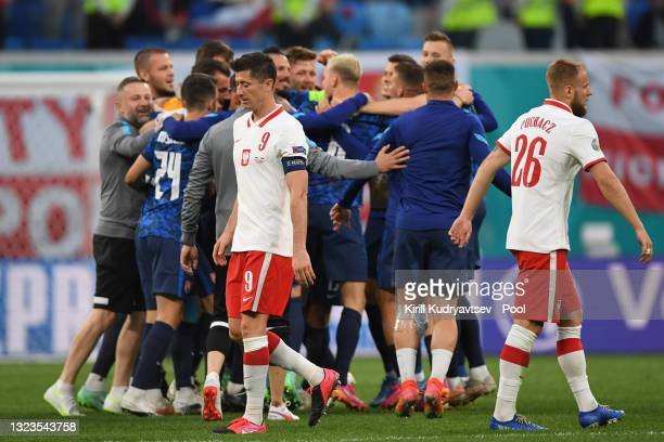 Robert Lewandowski of Poland looks dejected as Players of Slovakia celebrate after victory in the UEFA Euro 2020 Championship Group E match between...