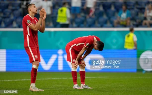 Robert Lewandowski of Poland looks dejected as teammate Jan Bednarek applauds the fans following defeat in the UEFA Euro 2020 Championship Group E...