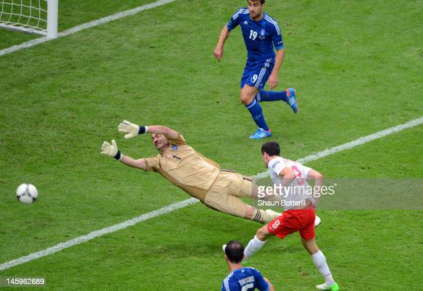 Robert Lewandowski of Poland scores the opening goal past Konstantinos Chalkias of Greece during the UEFA EURO 2012 Group A match between Poland and...