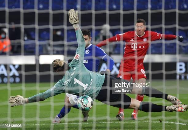 Robert Lewandowski scores their sides second goal past Ralf Fahrmann of FC Schalke 04 during the Bundesliga match between FC Schalke 04 and FC Bayern...