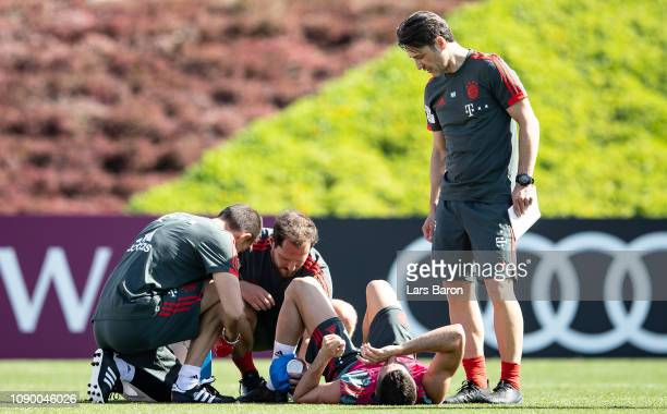 Robert Lewandowski sits injured on the pitch next to head coach Niko Kovac during a training session at day two of the Bayern Muenchen training camp...