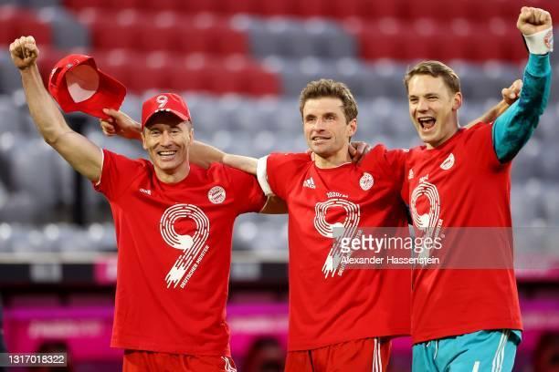 Robert Lewandowski, Thomas Mueller and Manuel Neuer of FC Bayern Muenchen celebrates winning the Bundesliga title after the Bundesliga match between...