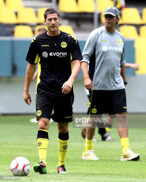 Robert Lewandowski walks past head coach Juergen Klopp during the Borussia Dortmund first training session for the upcoming season 2010/2011 at the...