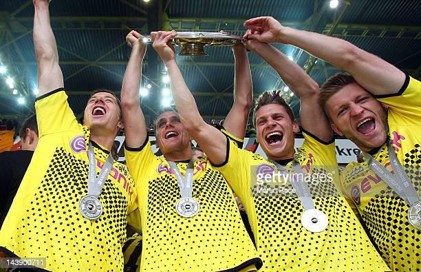 Robert Leweandowski Sebastian Kehl Lukasz Piszczek and Jakub Blaszczykowski celebrate with the trophy after winning the german championship after the...