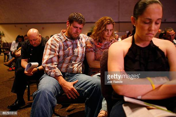 Robert Lewis and Darlene Zeh pray together as Kevin Cross delivers a sermon about faithbased financial management to a congregation at the Miami...