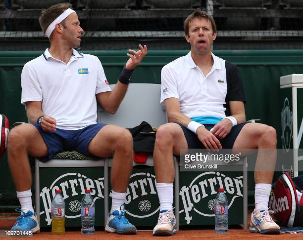 Robert Lindstedt of Sweden and Daniel Nestor of Canada talk as they take a break in their Men's Doubles match against Jonathan Dasnieres De Veigy and...