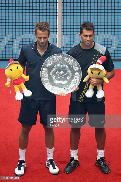 Robert Lindstedt of Sweden and Horia Tecau of Romania pose for photographers after winning the second place of the men's doubles final of the China...