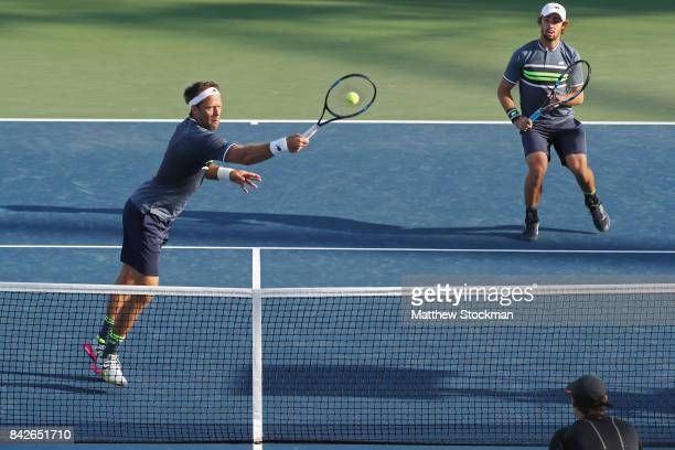 Robert Lindstedt of Sweden and Jordan Thompson of Australia return a shot against Jamie Murray of Great Britain and Bruno Soares of Brazil during...