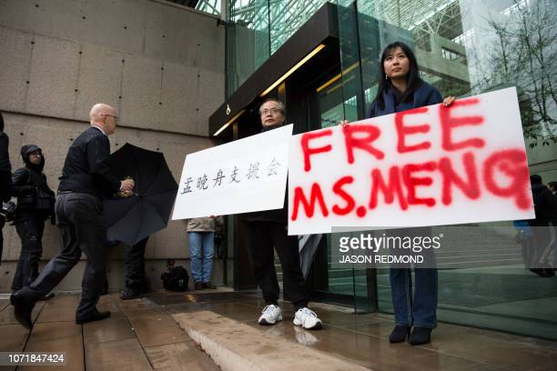 Robert Long and Ada Yu hold signs in favor of Huawei Technologies Chief Financial Officer Meng Wanzhou outside her bail hearing at British Columbia...