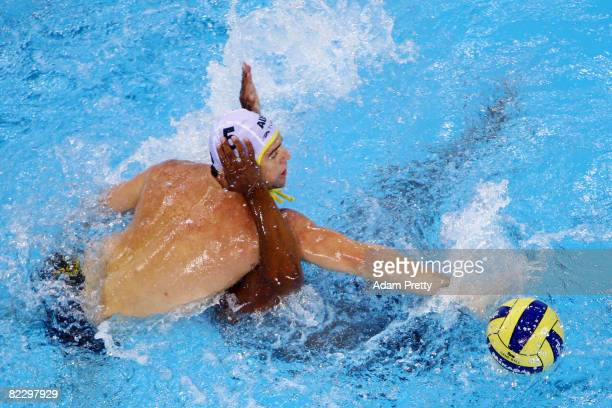 Robert Maitland of Australia reaches over Nathaniel Miller of Canada in the men's preliminary water polo event at the Olympic Sports Centre Yingdong...