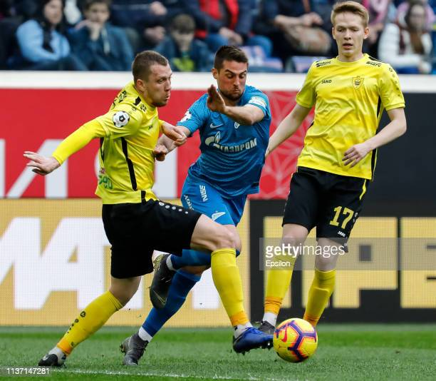 Robert Mak of FC Zenit Saint Petersburg vies for the ball with Vladislav Kulik and Ivan Ivanchenko of FC Anji Makhachkala during the Russian Premier...