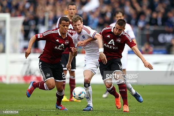 Robert Mak of Nuernberg and his team mate Timothy Chandler battle for the ball with Marcell Jansen of Hamburg during the Bundesliga match between...