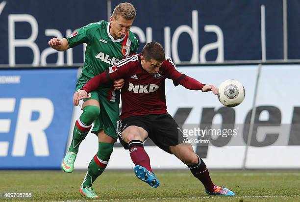 Robert Mak of Nuernberg is challenged by Matthias Ostrzolek of Augsburg during the Bundesliga match between FC Augsburg and 1 FC Nuernberg at SGL...