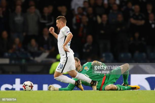 Robert Mak of Slovakia falls as he is faced by goalkeeper Craig Gordon of Scotland and is shown a second yellow card for simulation during the FIFA...