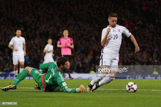 Robert Mak of Slovakia falls as he is faced by goalkeeper Craig Gordon of Scotland and is shown a second yellow card for simulation and is sent off...
