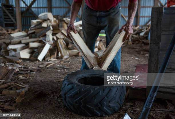 Robert Marble, 72 years, splits firewood logs in Charlotte, Vermont, August 12, 2018. Marble cuts, splits and stacks the wood by himself on a...
