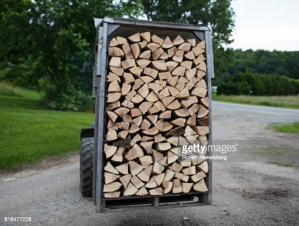 Robert Marble moves a halfcord of split firewood with a tractor June 29 2017 on his converted farm in Charlotte Vermont Marble is a firewood supplier...