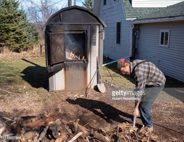 Robert Marble shovels wood pieces into his outdoor furnace which heats his home in Charlotte Vermont on April 11 2019 As owner of his firewood supply...