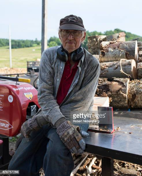 Robert Marble sits on his log splitter August 2 2017 in front of a pile of hardwood logs in Charlotte Vermont Marble is a firewood supplier who has...