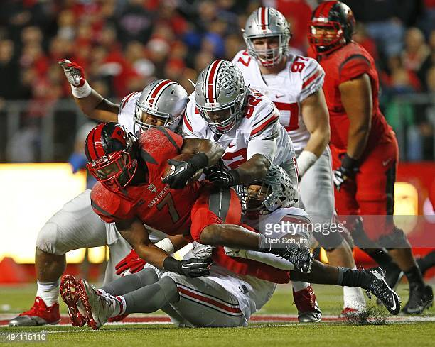 Robert Martin of the Rutgers Scarlet Knights is tackled by Adolphus Washington and Darron Lee of the Ohio State Buckeyes during the second period at...