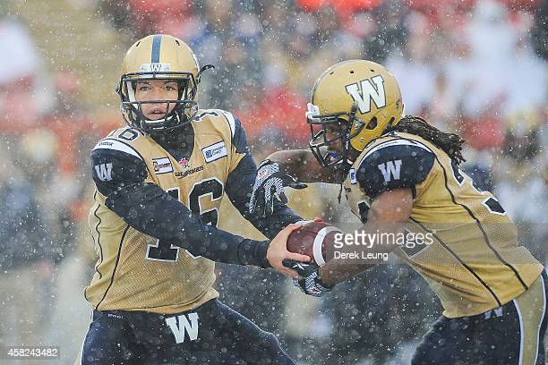Robert Marve of the Winnipeg Blue Bombers passes off the ball to teammate Paris Cotton during a CFL game against the Calgary Stampeders at McMahon...