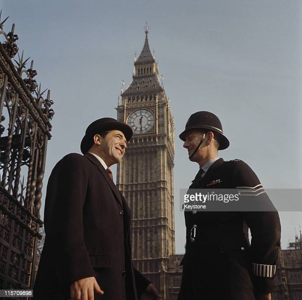Robert Maxwell stands talking to a police officer with Big Ben rising above them on his arrival at the Houses of Parliament to take his seat as MP...
