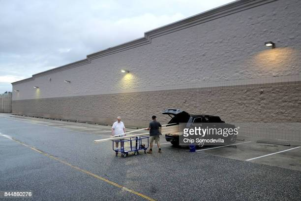 Robert McCarthy helps his son Brian McCarthy load lumber they plans to use to protect his home ahead of the arrival of Hurricane Irma outside the...
