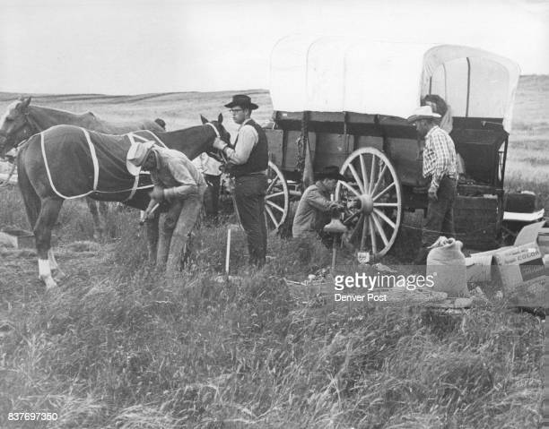 Robert Miller the wagon train blacksmith shoes horse held by Michael Owens 16 Jim Lake unscrews hub of wagon wheel to grease axle as Stanley Slocum...