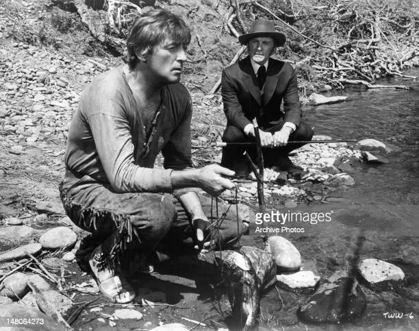 Robert Mitchum and Kurt Douglas squatting down by a river in a scene from the film 'The Way West' 1967