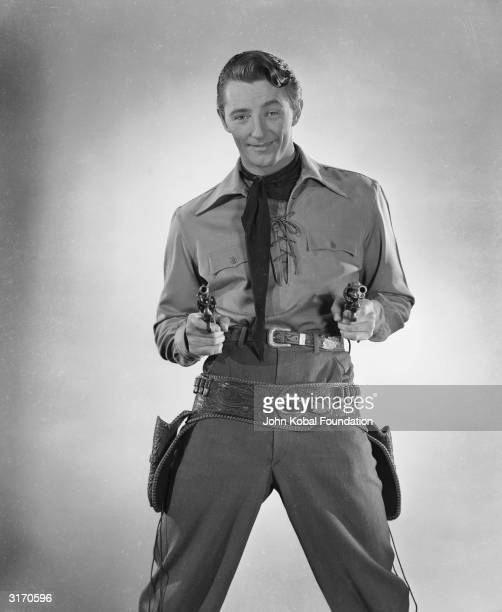 Robert Mitchum draws his pistols from their holster in the role of Pecos Smith in the film 'West of the Pecos' directed by Edward Killy