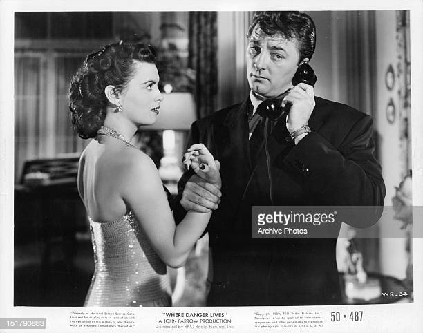 Robert Mitchum grabs the arm of Faith Domergue while on the phone in a scene from the film 'Where Danger Lives' 1950